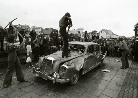 """Rúrí, Gullinn bíll, 1974. Gjörninginn flutti Rúrí á sýningunni """"Höggmyndir á þjóðhátíðarári, útisýning Myndhöggvarafélagsins í Reykjavík"""", á Lækjartorgi, árið 1974. Aðstoðarmenn við flutning: B. Gylfi Snorrason og óþekktir þátttakendur úr hópi áhorfanda. Ljósmynd: Ólafur Lárusson."""